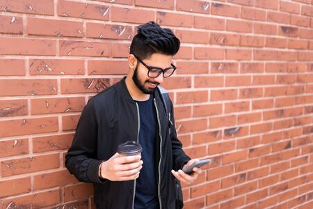 Handsome indian man use mobile phone enjoying coffee against brick wall Banque d'images