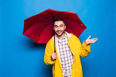 Young handsome bearded man in yellow raincoat with red umbrella trying to see if its raining over blue background