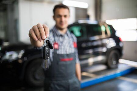 Mechanic handling keys of a car at the garage
