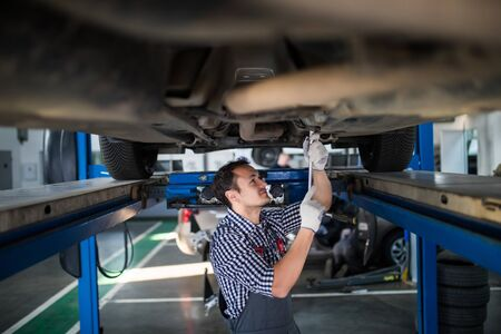 Male And Female Mechanics Working Underneath Car Together Stock Photo