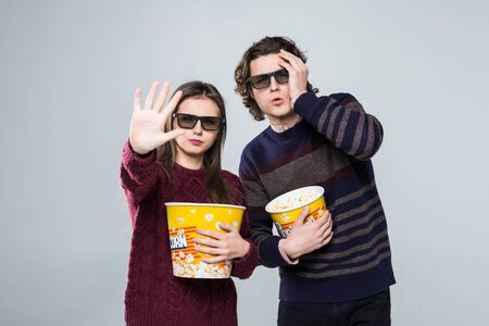 Young scared couple, woman and man in 3d glasses watching movie film on date holding buckets of popcorn covering faces with palm and screaming isolated on white background. Stock Photo