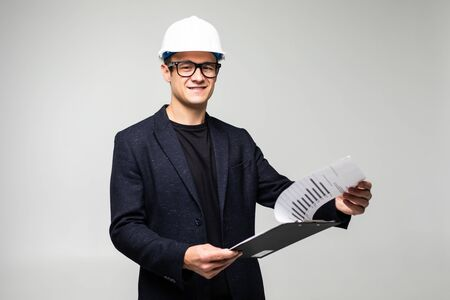 Happy male architect writing notes on clip board against white background