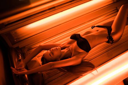 Young beautiful lady lying on a tanning bed at health spa