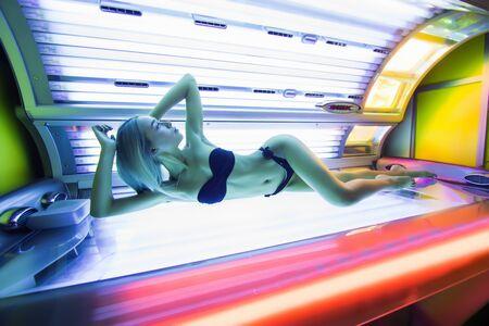 Beautiful woman lying in solarium and sunbathing
