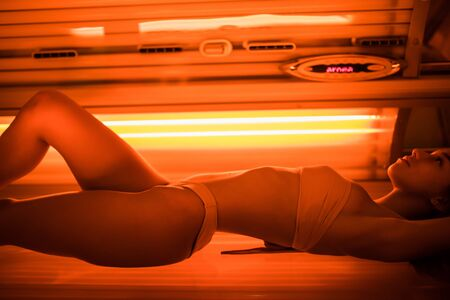young woman at laying on solarium bed and get brown skin tone ready for summer 스톡 콘텐츠