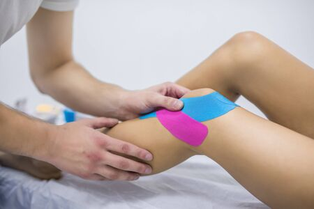 Physical therapy - therapist placing tape on patient's knee