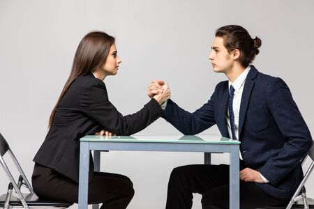 Business couple are fighting in their arms, arm wrestling between male and female. Family quarrel, showdown, division of property, divorce.