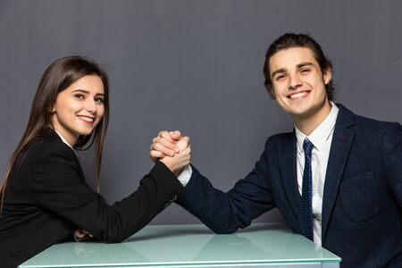 Beautiful business couple doing arm wrestling challenge on gray background