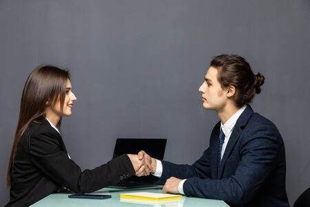 Young beautiful couple of business workers smiling happy and confident. Shaking hands with smile on face for agreement at office Imagens - 142513826