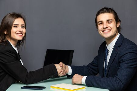 Young beautiful couple of business workers smiling happy and confident. Shaking hands with smile on face for agreement at office Imagens - 142513877