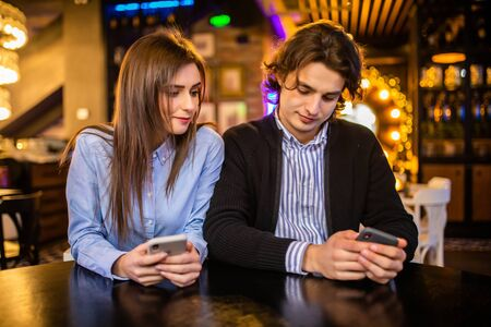 phubbing, always connected, internet addiction, young couple in cafe looking at their smartphones, social network concept
