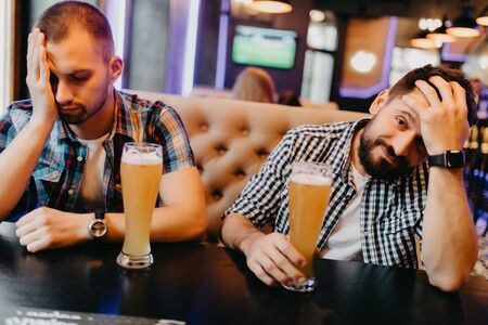Two men drink beer sad after experiencing their favorite team the pub