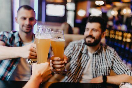Menschen, Männer, Freizeit, Freundschaft und Feierkonzept - glückliche männliche Freunde, die Bier trinken und an der Bar oder Kneipe anstoßen