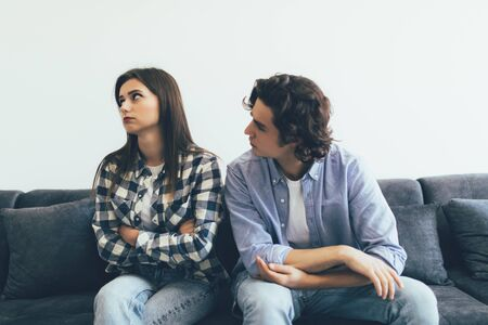 Quarreled couple sitting on the sofa in their living room Imagens - 142514114