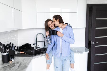 Beautiful young couple is hugging and smiling while drinking tea in kitchen at home. Man is kissing his charming girl