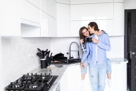 Young man and woman family standing in the kitchen together hugging kissing driking coffee holding cups Imagens - 142515129