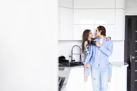 Young man and woman family standing in the kitchen together hugging kissing driking coffee holding cups Imagens - 142515130