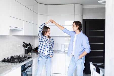 Happy couple dancing in kitchen at home