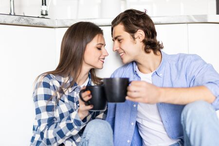 Happy young man and woman sitting on kitchen floor. Romantic young couple sitting on kitchen floor in morning. Imagens - 142515213