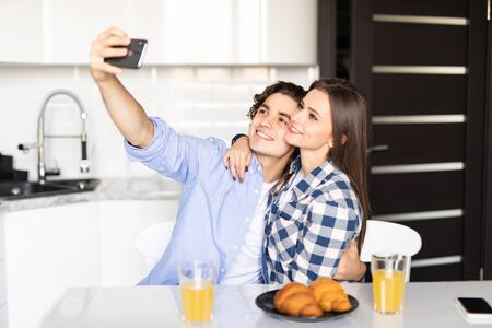 Beautiful couple is doing selfie using a smart phone and smiling while having a breakfast at home Imagens - 142515225