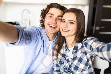 Morning family fun. Closeup portrait of couple drinking coffee in kitchen, using smartphone camera to take selfie. Imagens - 142515229