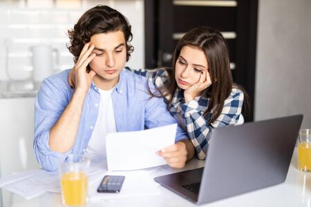 Young couple with many debts doing paperwork together, reviewing their bills, planning family budget and calculating finances at kitchen table with papers, calculator and laptop computer Imagens - 142515615