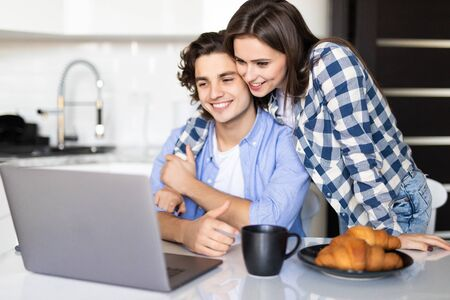 cheerful couple having breakfast and using laptop in morning Imagens - 142515645
