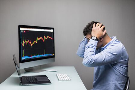 Man lamenting with hands on the head in front of computer with graph of unsuccessful business on the screen.
