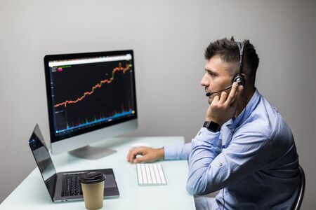 Side view of stock market broker looking at graphs on multiple screens in office