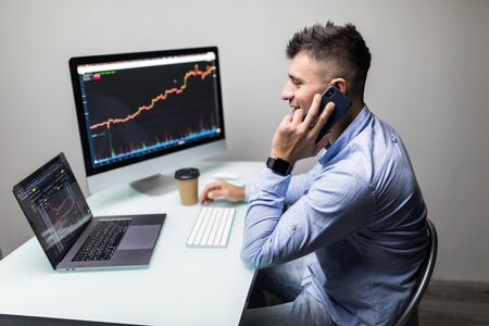 Smiling young male online stock trader talking on smartphone with client while using laptop at desk Imagens