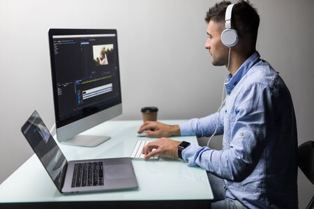 Male videographer edits and cuts footage and sound on his personal computer at his office