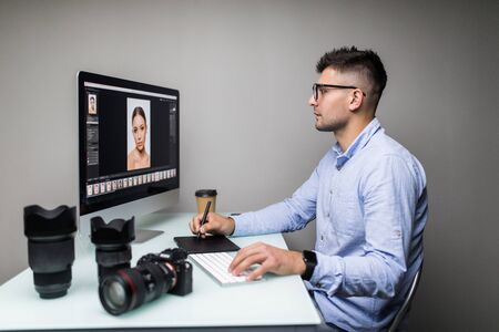 Rear view of a casual male photo editor using graphics tablet in office