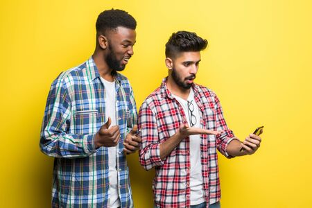 Portrait of a two cheerful young men looking at mobile phone over yellow background