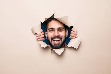 Young indian bearded man smile look from beige paper hole Foto de archivo