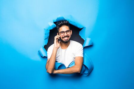Young handsome indian man talk phone look from blue paper hole