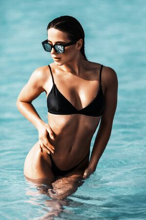 Young pretty woman in black bikini standing in sea water. 版權商用圖片