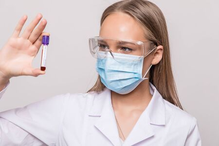 Positive blood test result doctor in protective medical mask, rubber gloves and lab coat on gray background. Respiratory Syndrome concept. Archivio Fotografico