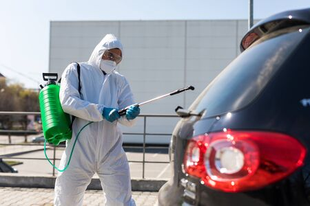 Disinfector in a protective suit and mask sprays disinfectants of car outdoors. Coronavirus Pandemic.