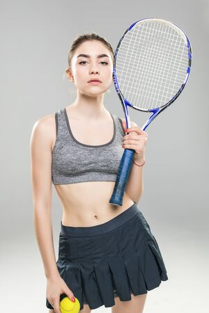 Cropped image of a confident woman tennis player holding racket and ball isolated over gray background 免版税图像