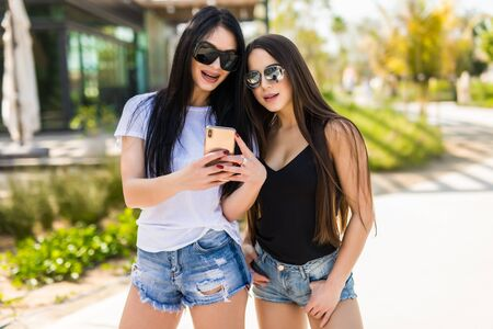 Female friends wearing sun glasses and smile widely as they take a photo with their cell phone 写真素材