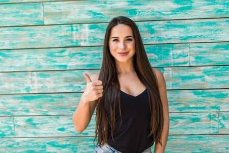 Smiling woman with thumbs up standing near to green wall
