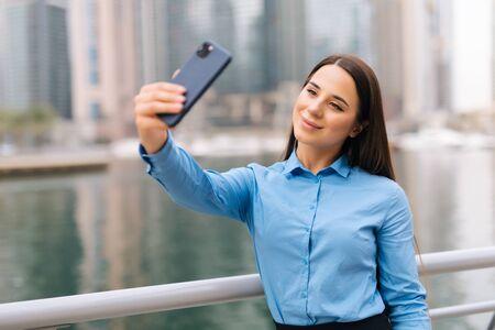 Business woman making selfies in front of office building. Standard-Bild
