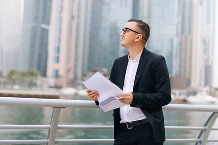 Handsome young man in suit reading contract while standing outdoors