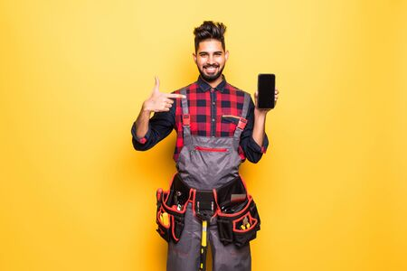 Portrait of indian handyman showing screen of mobile phone on yellow background