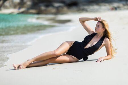 Fashion woman in black swimwear lying on tropical beach. Portrait of beautiful young woman lying on side enjoying sunbath near the sea shore. Sexy tanned girl in stylish swimsuit looking at camera.