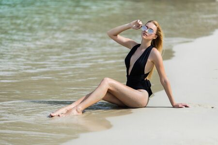 Young woman in a black swimsuit. Beautiful woman sitting on a sand.