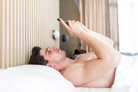 man use smartphone from the early morning. whole world in phone. he is blogging. flirting and sending text message. internet addiction and mobile abuse concept. man in bed chatting.