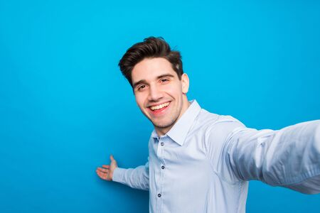 Handsome brunet young man is making selfie and smiling on blue background