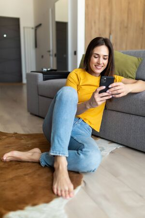 Young woman texting on smartphone. Pretty woman in casual looking at away while sitting on the floor carpet with tablet.
