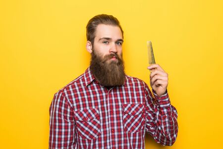 Happy hipster man comb his beard and moustache on yellow background.